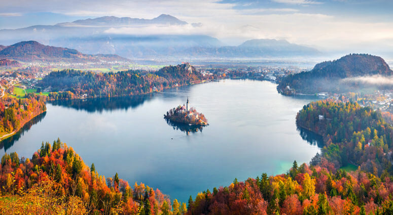Aerial view of church of Assumption of Maria on the Bled lake. Sunny autumn landscape in Julian Alps