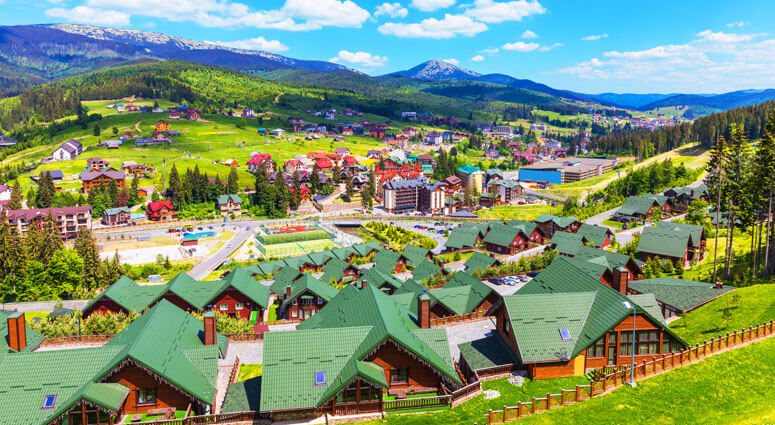 Scenic summer view of winter ski resort with house and cottage in Bukovel, Carpathian Mountains, Ukraine