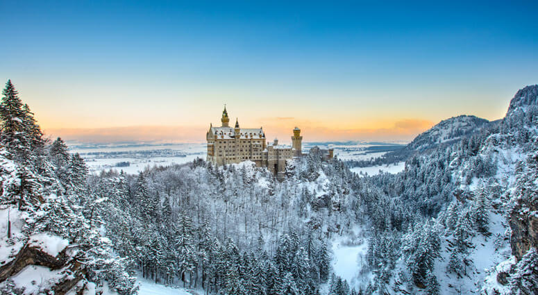 The famous Neuschwanstein Castle in the background of snowy mountains and hills in beautiful sunrise light. Germany, Europe
