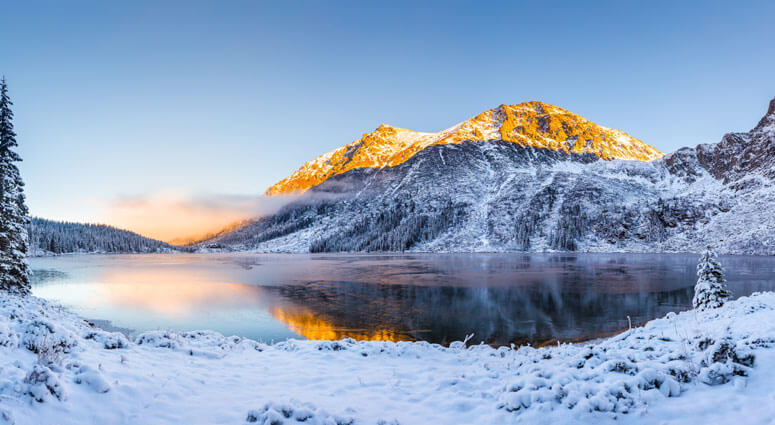 Winter landscape. Winter natural background. Mountains with snow covered hills and sunny peaks by the lake. Tatras, Zakopane, Poland